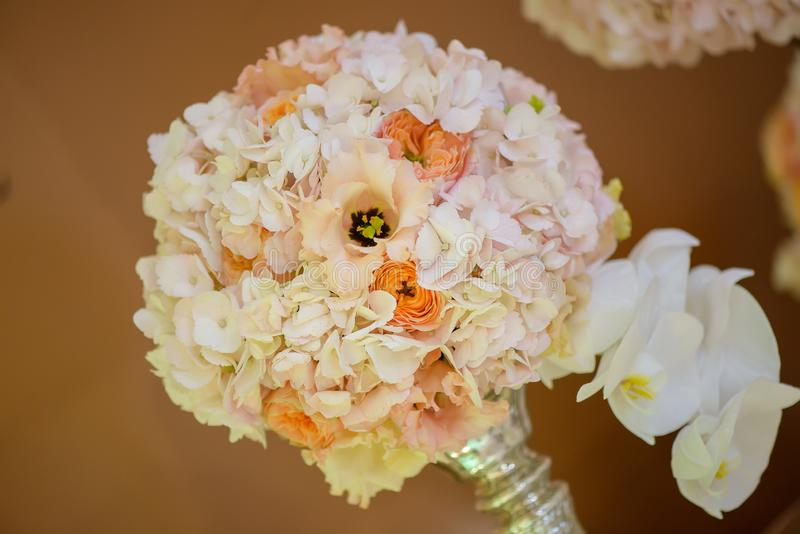 Classy floral arrangement in a pastel round bouquet featuring pink hydrangea roses and orchids stock photos
