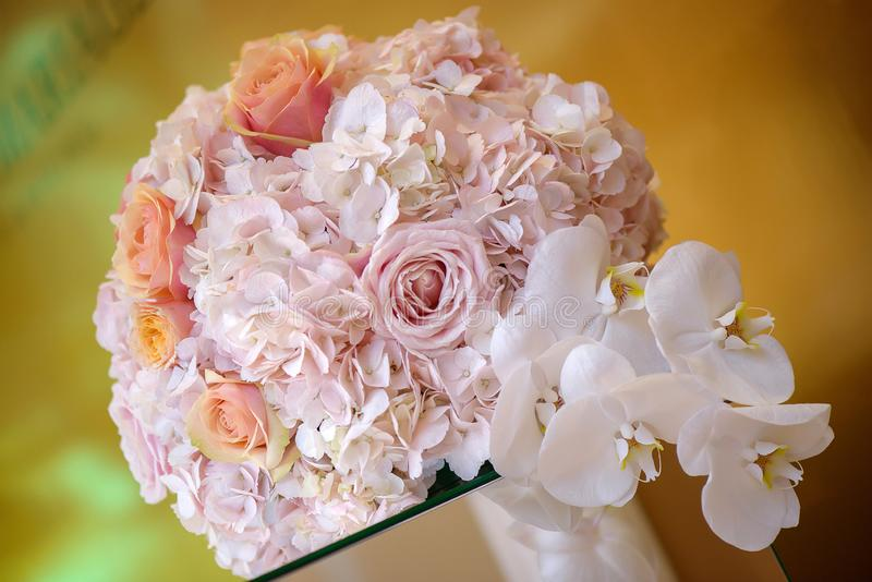 Classy floral arrangement in a pastel round bouquet featuring pink hydrangea roses and orchids stock photo