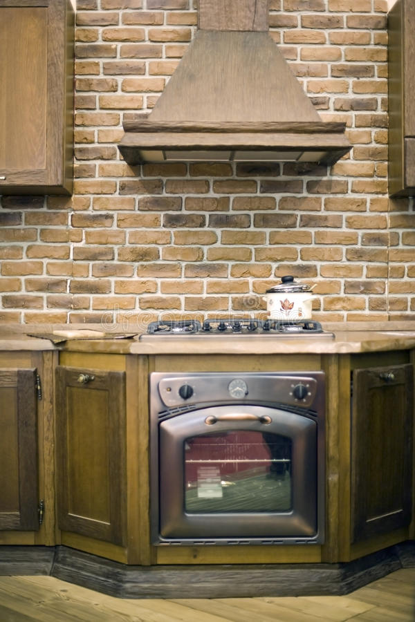 Classy Kitchen Interior detail. The interior of a rustic country kitchen featuring an elegant stove with built-in wooden cabinetry and marble counter tops royalty free stock image