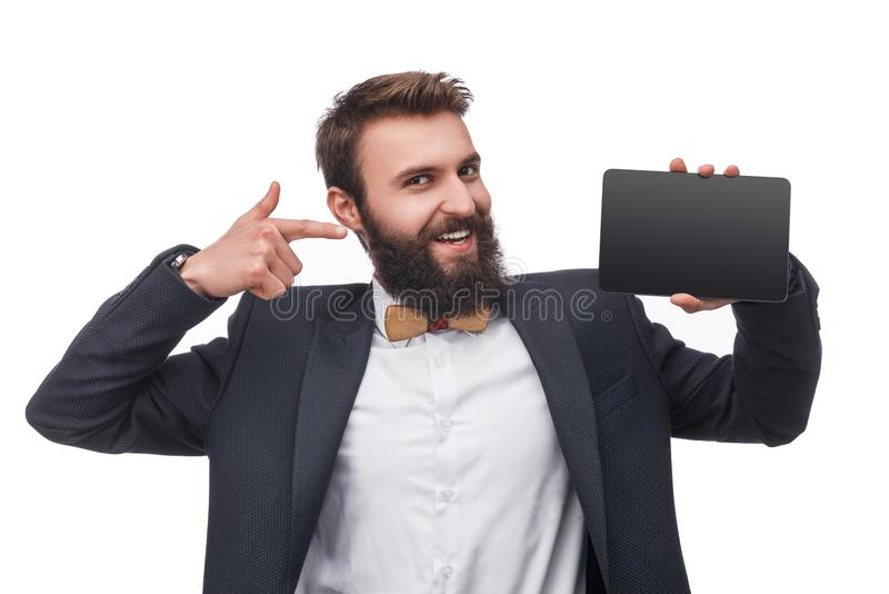 Classy man pointing at new tablet. Cheerful bearded man in modern elegant suit showing new tablet and pointing at it isolated on white background royalty free stock photo