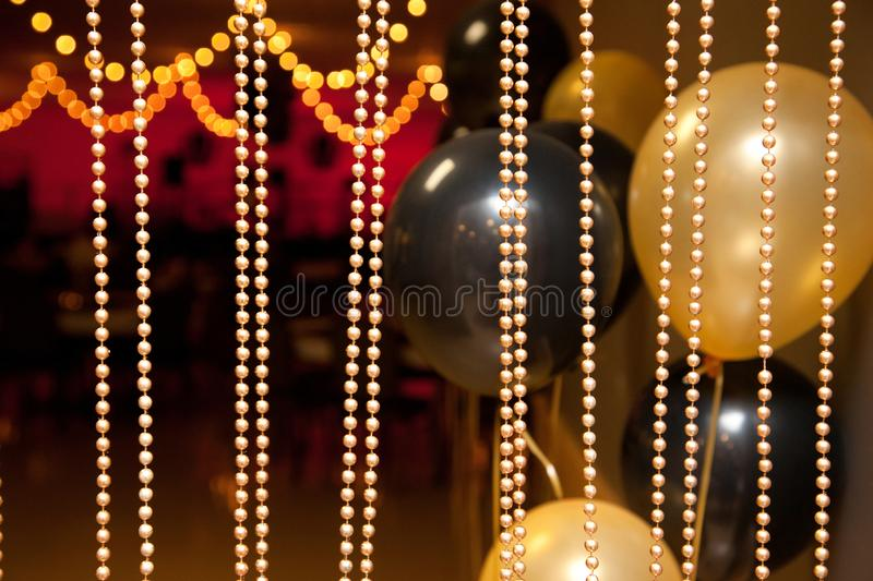 Classy party decor with black and gold. Balloons coloured in black and gold with gold beads streaming and copy space stock image
