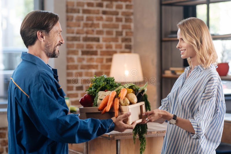 Classy polite woman thanking for delivery. Serving people. Sincere young charming lady receiving her purchase at home while courier handing her a box full of royalty free stock image