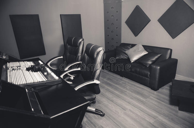 Classy professional recording studio setup, large desk with mixing console and two chairs, window for vocal booth, sofa stock photo