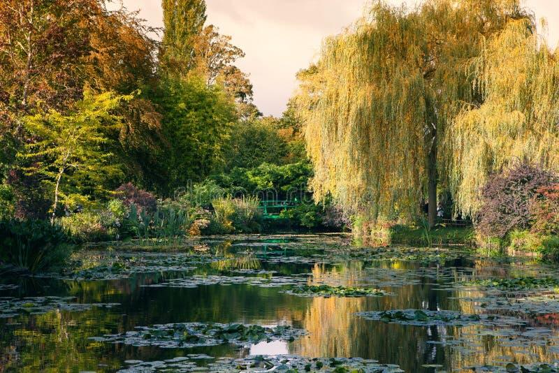 Claude Monet el jardín en otoño, lirios de agua en el lago en un día soleado foto de archivo