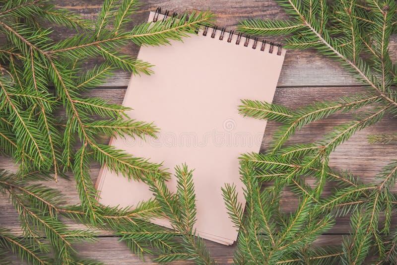 claus meddelande santa till Filialer för julgranträd på träbräde med den tomma anteckningsboken Jul eller ram för nytt år för din arkivbild
