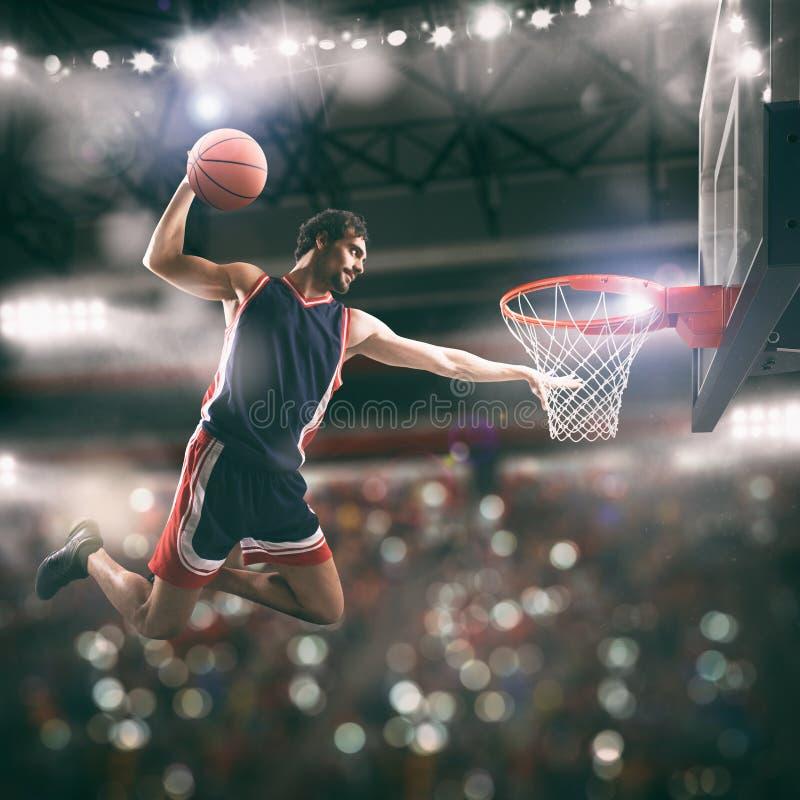 Clavada acrobática de un jugador de la cesta en la cesta en el estadio fotos de archivo