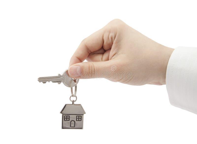 Clave de la casa a disposición aislado en blanco imagenes de archivo
