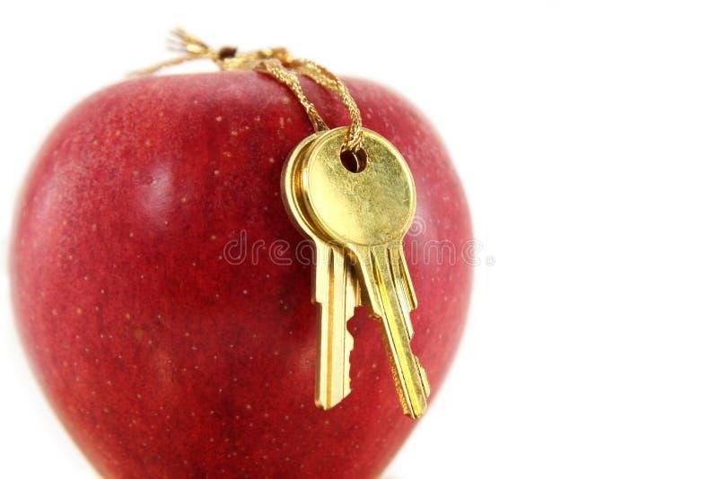 Clave de oro y manzana roja imagen de archivo