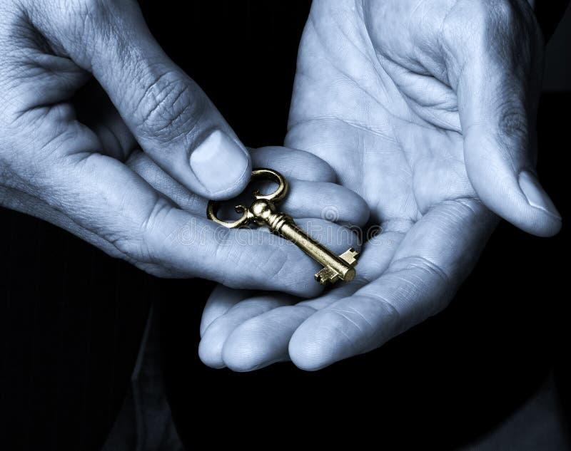 Clave del oro en manos fotos de archivo