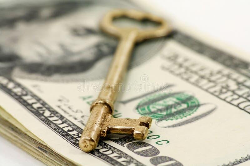 Clave y dólares del oro imagen de archivo