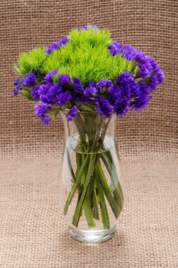 Clavel verde Barbatus Sweet William de la bola y flores púrpuras oscuras del sinuatum del Limonium de Statice en la arpillera nat imagen de archivo libre de regalías