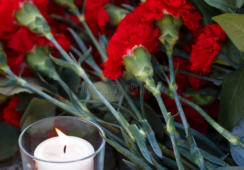 Claveles rojos y vela blanca Recuerde de terror de las víctimas imágenes de archivo libres de regalías