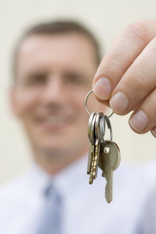 Claves de entrega del agente inmobiliario fotos de archivo