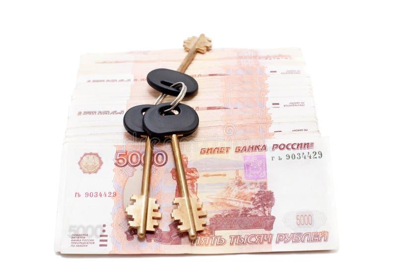 Claves de la casa en el dinero fotos de archivo