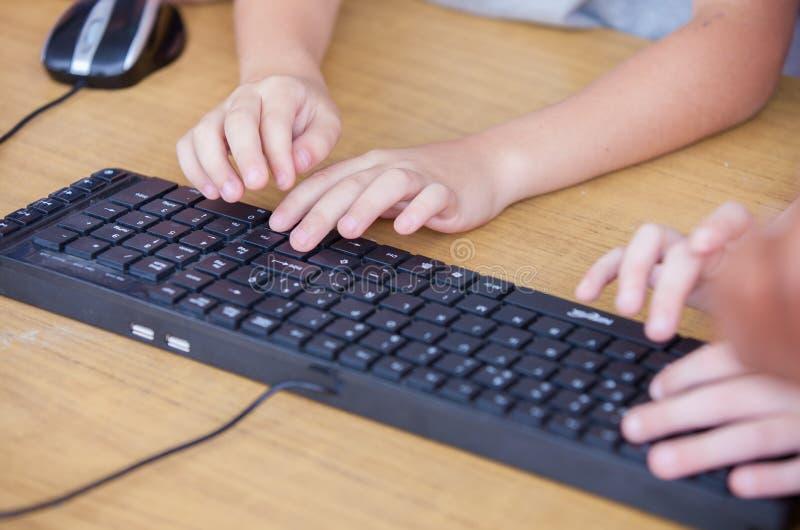 Clavier d'ordinateur avec des mains d'enfants photo libre de droits