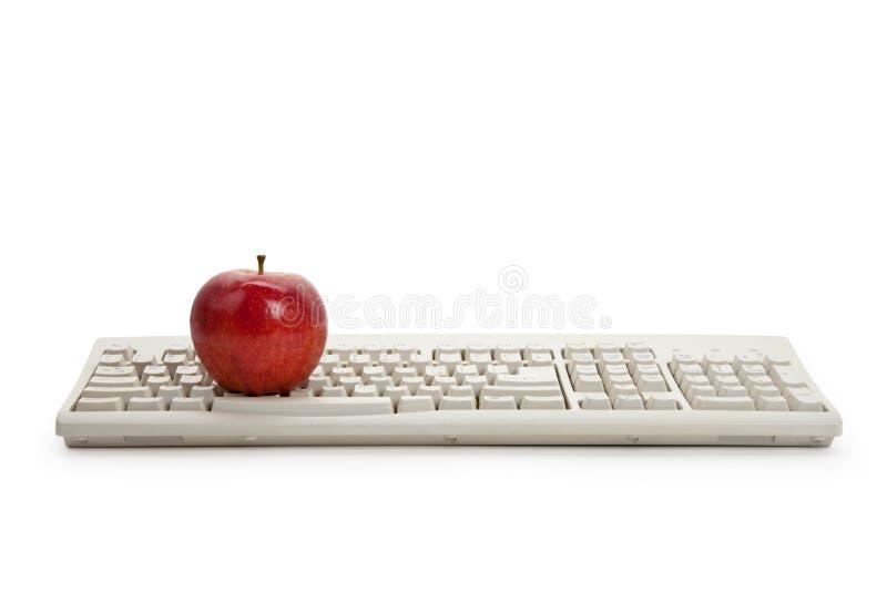 Clavier d'ordinateur et pomme rouge photographie stock libre de droits