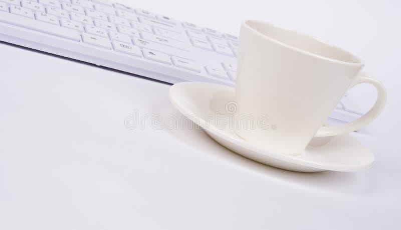Clavier d'ordinateur et tasse, vue de côté images stock