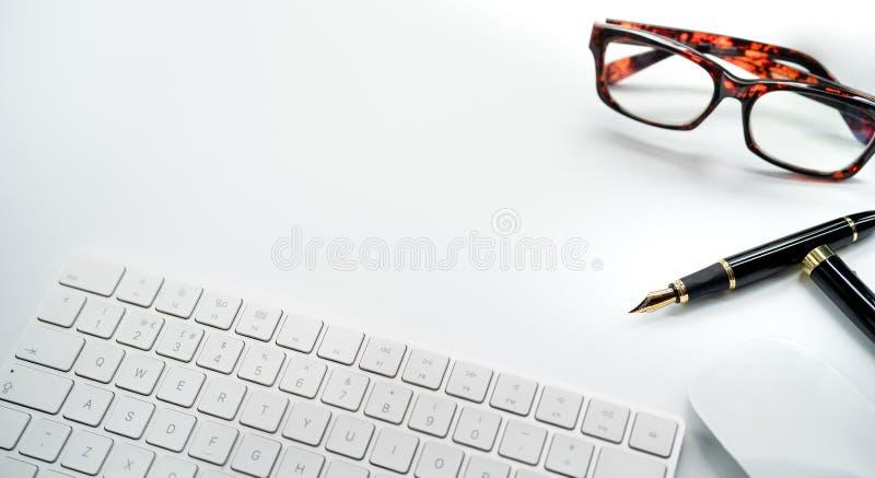 Clavier et souris d'ordinateur avec de diverses fournitures de bureau sur le bureau blanc avec l'espace de copie photographie stock
