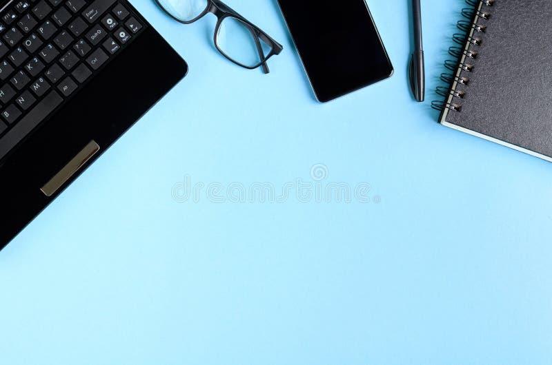 Clavier noir en verre, de téléphone portable, de carnet et d'ordinateur portable sur la composition bleue en fond images stock