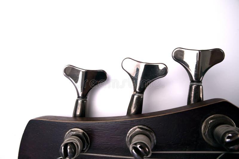 Clavijas de la guitarra baja en el jefe del primer del cuello imagen de archivo