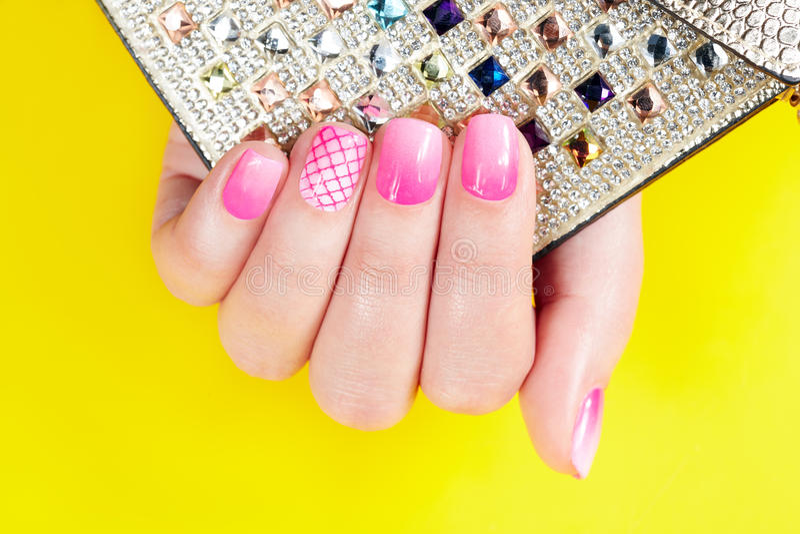 Clavos con la manicura cubierta con el esmalte de uñas rosado, fondo amarillo foto de archivo libre de regalías