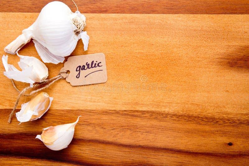 Clavos de ajo con la etiqueta en tabla de cortar de madera imágenes de archivo libres de regalías