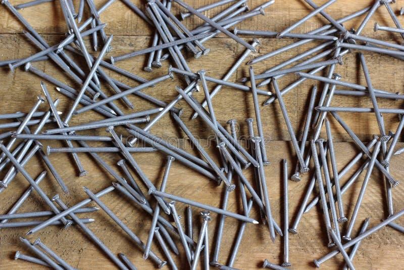 Clavos de la techumbre dispersados en el suelo de madera imagen de archivo