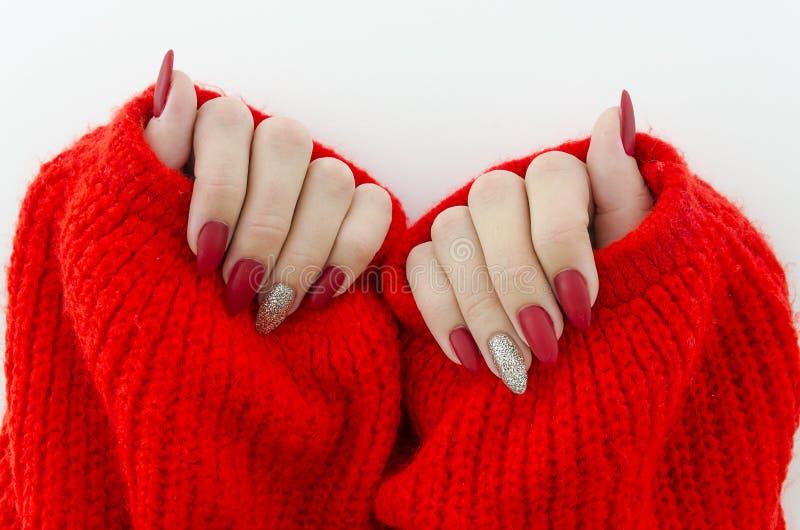 Clavos femeninos hermosos del finger con cierre rojo del clavo para arriba en el suéter hecho punto rojo Manicura perfecta fotos de archivo libres de regalías