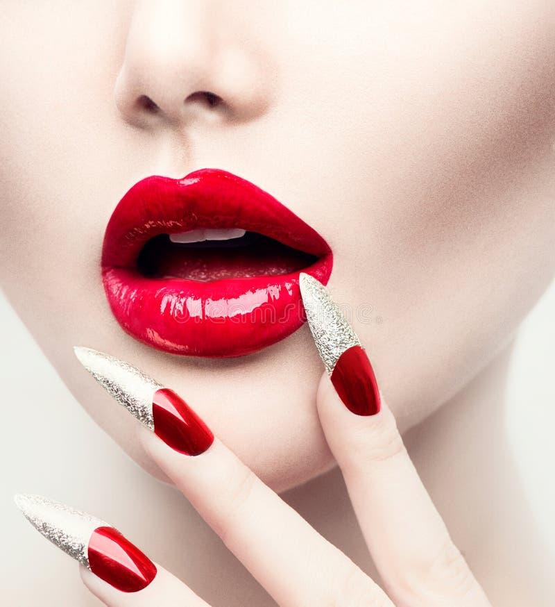 Clavos largos rojos y labios brillantes rojos fotos de archivo libres de regalías