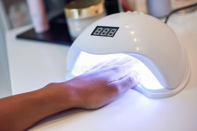 Clavos Manicured en lámpara ULTRAVIOLETA en salón de belleza foto de archivo libre de regalías