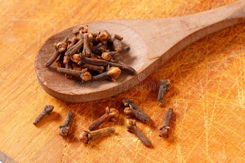 Clavos secados en la cuchara de madera imagenes de archivo