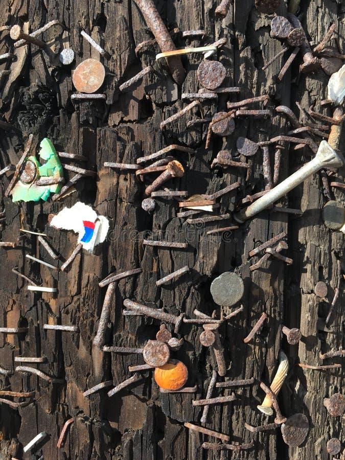 Clavos y grapas y pedazos al azar de la materia enviados en posts de la lámpara imagen de archivo