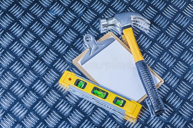 Claw hammer and construction level clipboard on corrugated metalic sheet royalty free stock photography