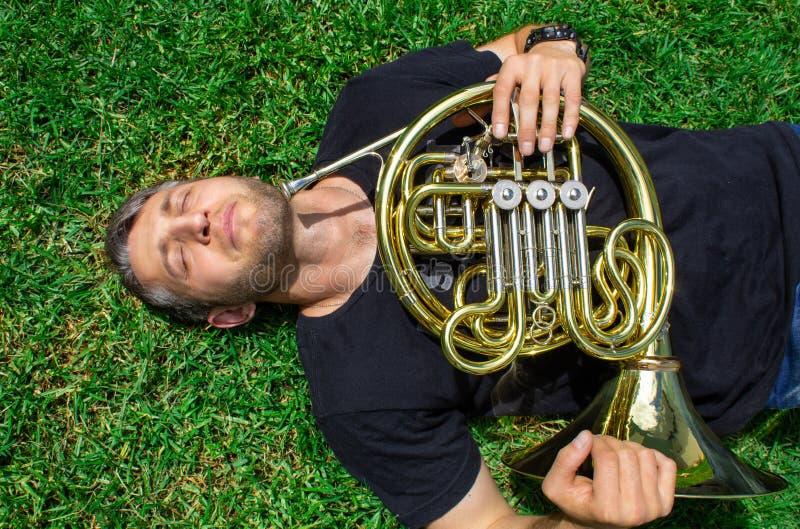 Claxon francés Un hombre en una camiseta miente en la hierba y sostiene un instrumento musical Waldhorn fotos de archivo