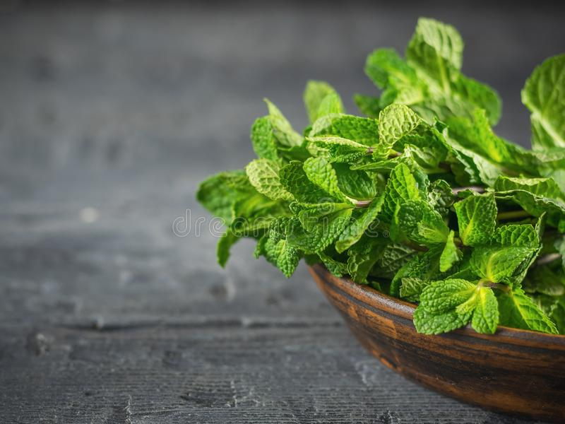Clay bowl with a bunch of fresh mint on the black wooden table. The concept of healthy eating. stock photos