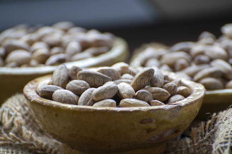 Clay bowls with dried pistachio nuts close up. Clay bowls with dried pistachio nuts in shell close up royalty free stock photo