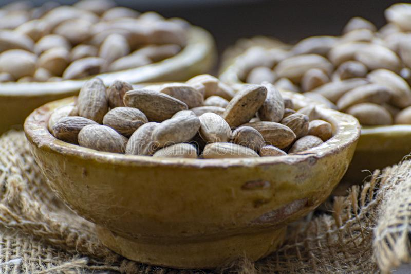 Clay bowls with dried pistachio nuts close up. Clay bowls with dried pistachio nuts in shell close up royalty free stock images