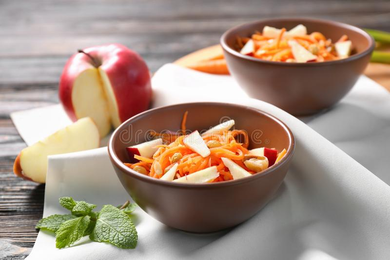 Clay bowls with yummy carrot raisin salad with apple. On kitchen table royalty free stock image