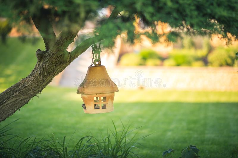Clay or ceramic bird feeder hanging on a tree in the garden, soft blurry background. Clay or ceramic bird feeder hanging on a tree, soft blurry background royalty free stock photo