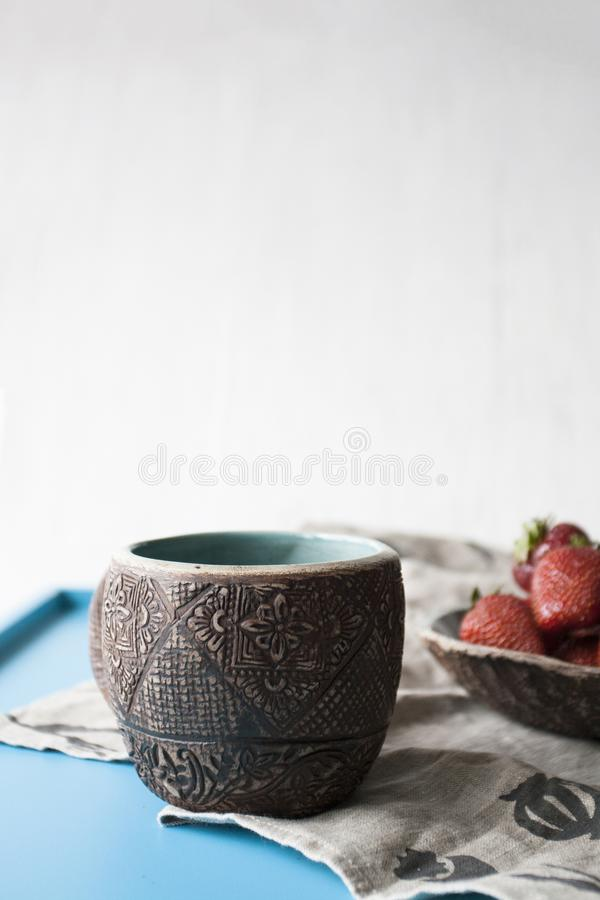 Clay cup with coffee or tea and a plate of strawberries. In the background stock images