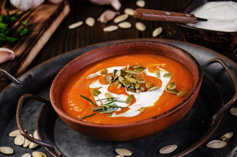 Clay dish with homemade rustic pumpkin soup with seeds on metal tray with seeds and greens aside.  stock photo