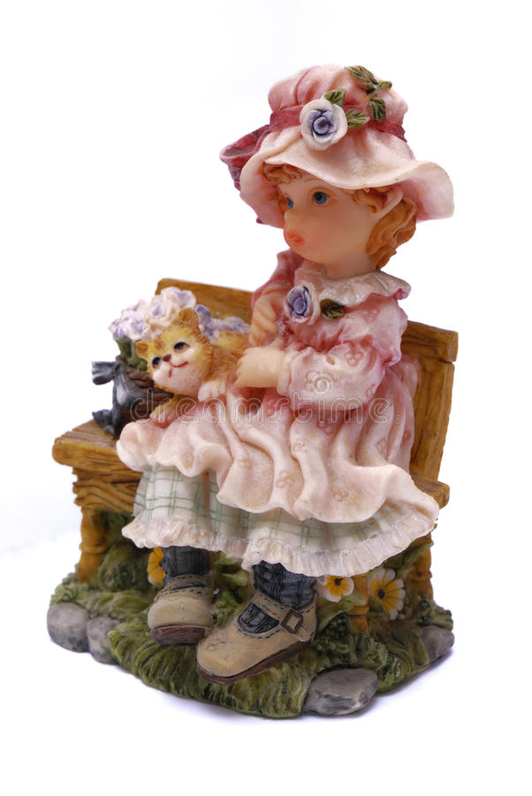 Clay doll display of a young girl and a cat sitting on a wooden bench stock photos