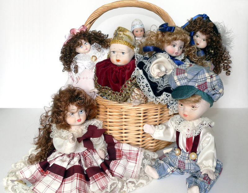 Clay dolls. A wicker basket with lonely clay dolls over white royalty free stock images