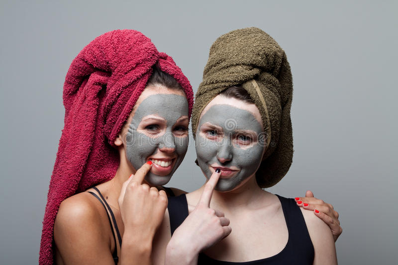 Clay facial mask. Two happy sisters stock photography