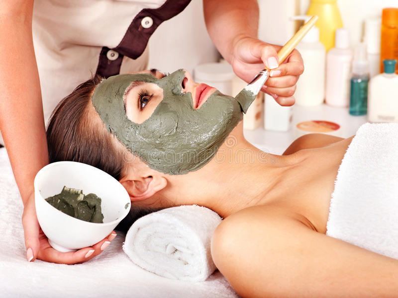 Clay facial mask in beauty spa. Woman with clay facial mask in beauty spa stock photos