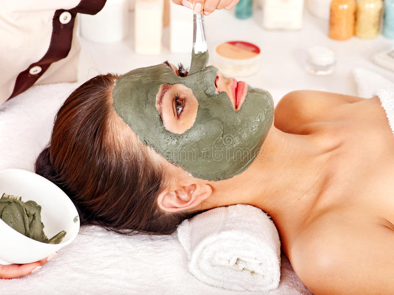 Clay facial mask in beauty spa. Woman with clay facial mask in beauty spa royalty free stock image