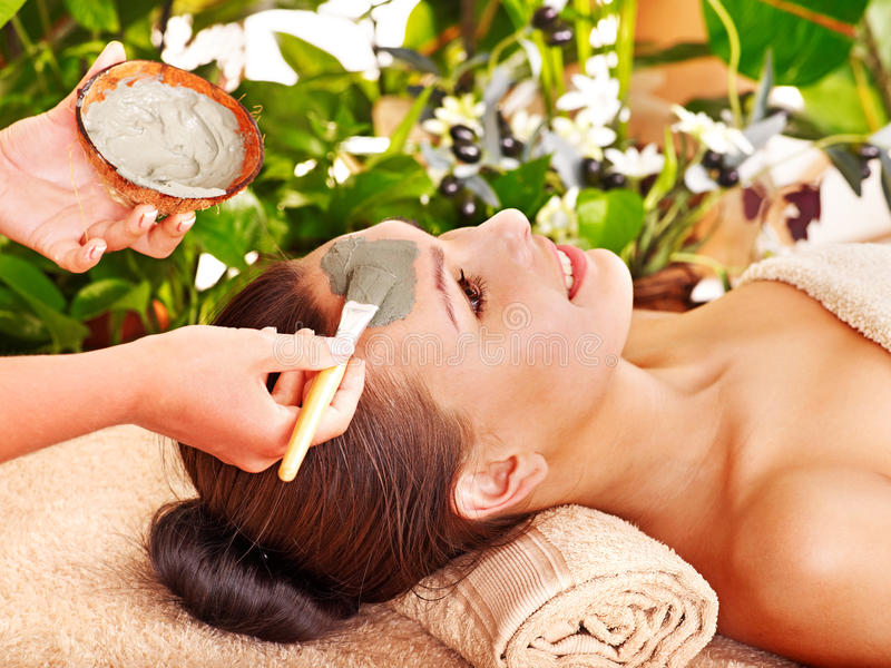 Clay facial mask in beauty spa. Woman with clay facial mask in beauty spa royalty free stock photography
