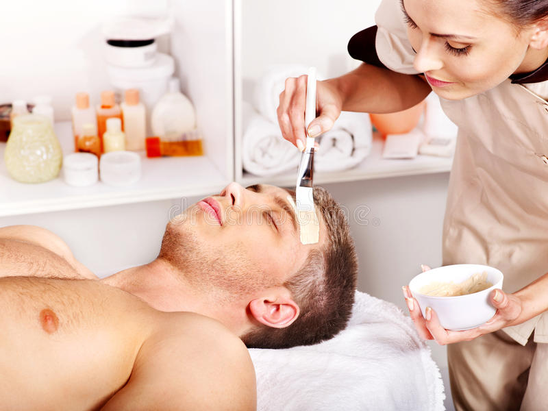 Clay facial mask in beauty spa. Man with clay facial mask in beauty spa royalty free stock image