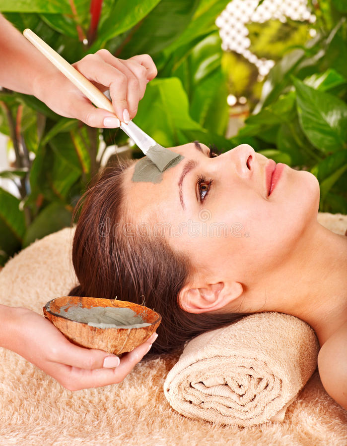 Clay facial mask in beauty spa. Woman with clay facial mask in beauty spa royalty free stock images