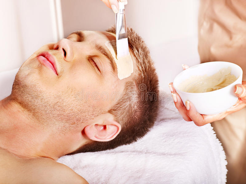 Clay facial mask in beauty spa. Man with clay facial mask in beauty spa royalty free stock photography